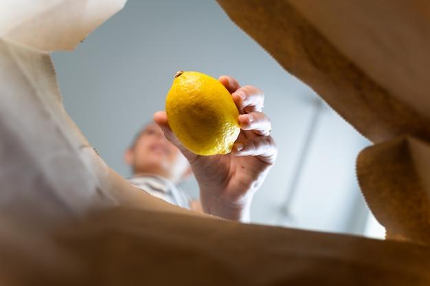 Внутренний вид крафт-бумаги с женщиной кладет в нее еду. концепция еды забрать
