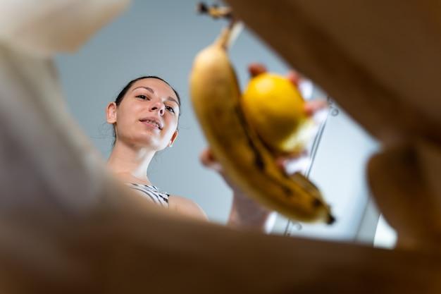 女性と一緒にクラフトペーパーバッグの内部ビューは、それに食品を入れます。食べ物を奪うコンセプト