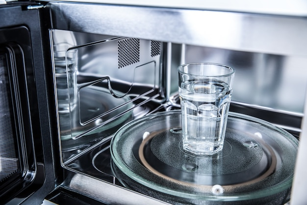 깨끗한 물 한 컵과 함께 새로운 깨끗한 staniless, 전자레인지의 내부 보기.