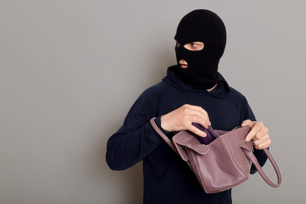 Insidious male villain in balaclava stands with stolen women's bag and wallet