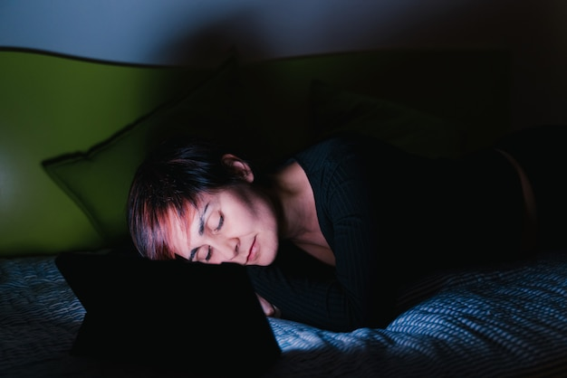 不眠症と不眠生活。ベッドでテレビを見て寝ている若い白人女性。人々は寝る前に娯楽機器に接続しました。テクノロジーとレジャーのコンセプト。