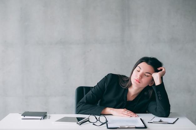 불면증과 초과 근무. 사무실 책상에서 자 고 피곤 된 젊은 비즈니스 여자의 초상화.