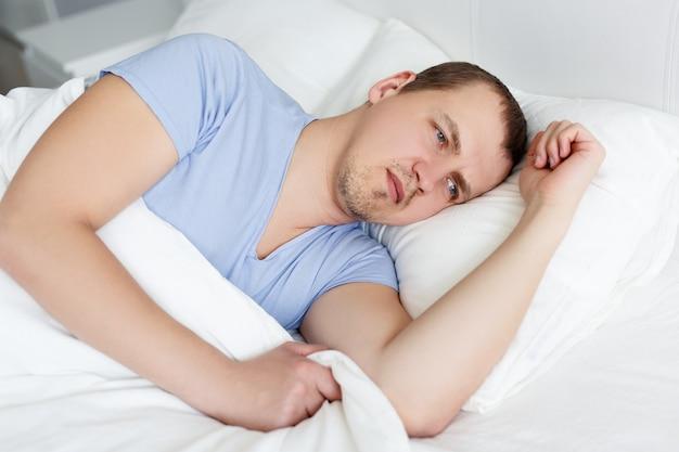不眠症の概念-自宅のベッドに横たわっている疲れた男の肖像画