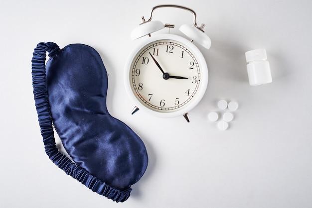 不眠症、うつ病、睡眠障害の概念。目覚まし時計、白い背景の上の睡眠マスクと丸薬、上面図