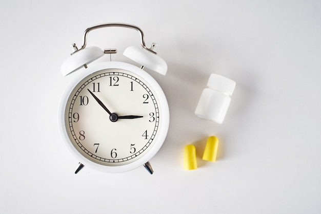 Insomnia problem concept. alarm clock, ear plugs and pills on white background