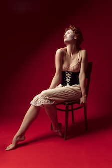 Insomnia at summer night. medieval redhead young woman as a duchess in black corset and night clothes sitting on the chair on red wall. concept of comparison of eras, modernity and renaissance.