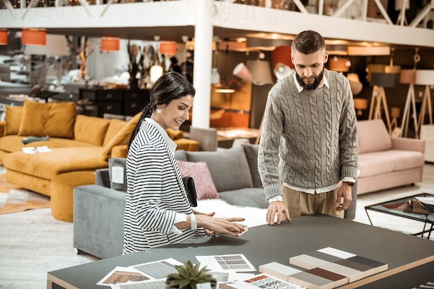 Inspecting colorful samples. bearded focused man showing his wife wooden pieces and discussing color of table surface
