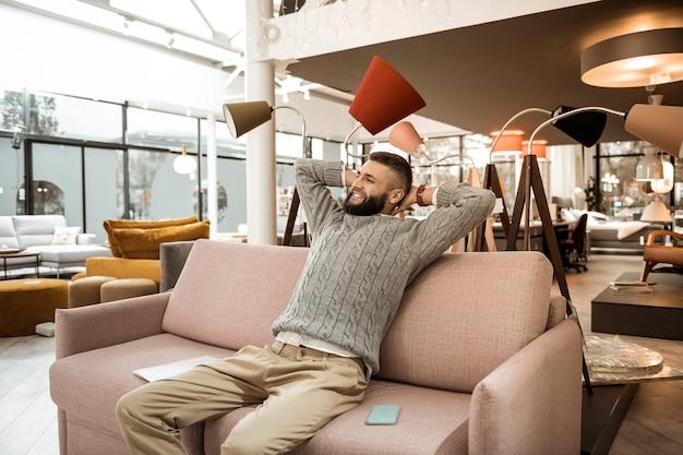 書類の検査。買い物に飽き飽きし、ソファでくつろぎながらストレッチをするうれしそうな男