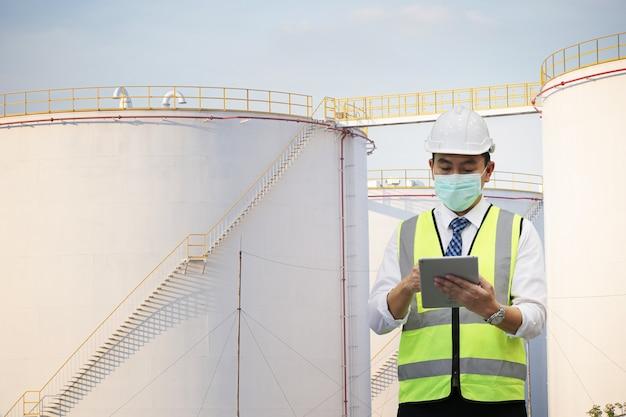 Инженер-инспектор держит планшетный компьютер у топливных баков на промышленной площадке.