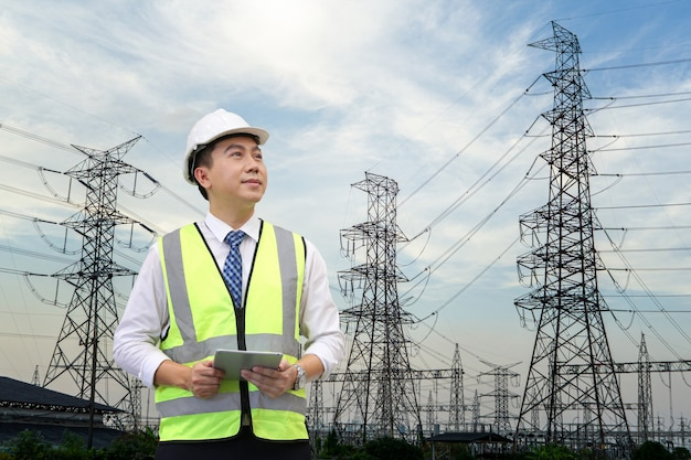 Inspection engineer holding tablet computer against high electric power at industry site. Premium Photo