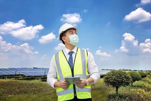 현장에서 전력을 공급하기 위해 태양광 발전소에 태블릿 컴퓨터를 들고 있는 검사 엔지니어.