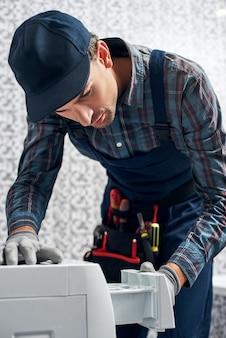 Inspection look working man plumber in bathroom checking washing mashine