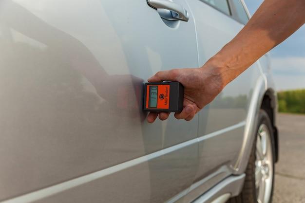 자동차의 본체와 보닛의 검사 남자는 기구로 자동차 본체를 측정합니다