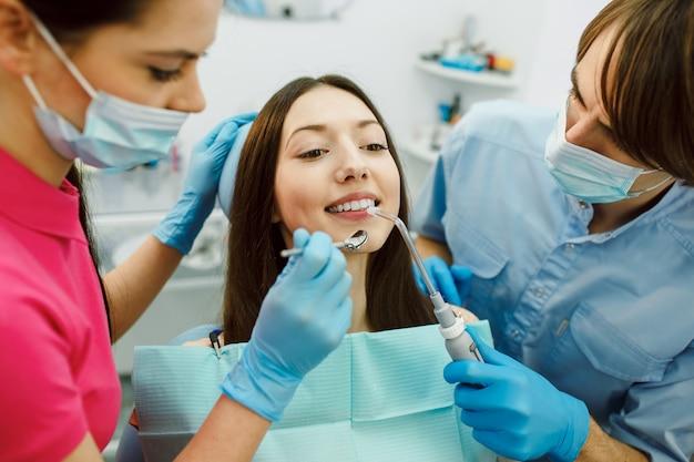 Осмотр зубов женщины с помощью зеркала.