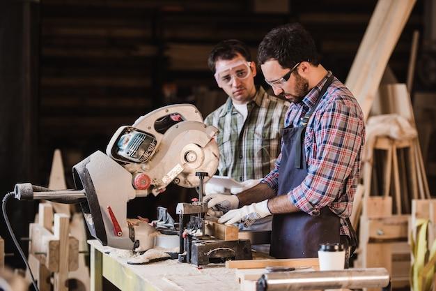 検査官と大工が家具用木製品の製造プロセスについて話し合う