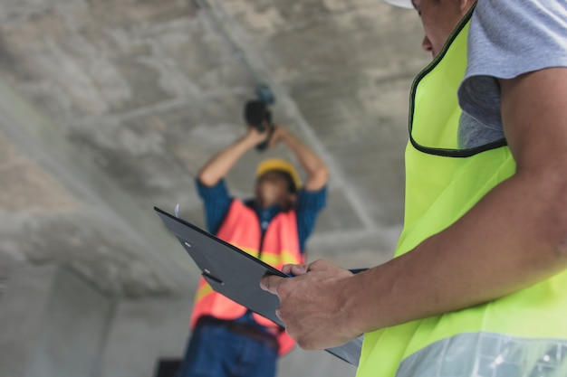 Inspector checking worker working in construction site
