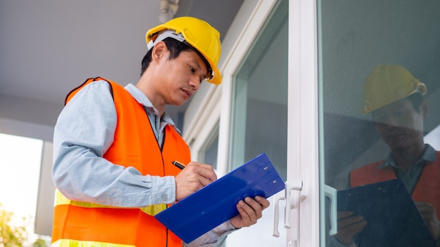 The inspector or engineer is checking the building structure and door specifications. after renovation is complete