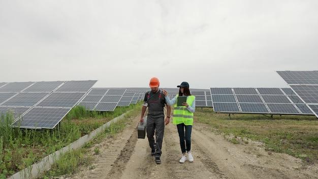 검사관 엔지니어 여성과 보호 헬멧을 쓴 남성 엔지니어가 태양광 발전소를 걷습니다.