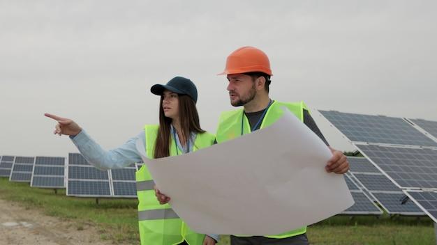 검사 엔지니어 여성과 남성 엔지니어가 프로젝트 도면에 대해 논의하고 있습니다. 그들은 태양 전지 패널 스테이션에 서 있습니다. 여성 엔지니어가 손으로 물체를 가리키고 있습니다.
