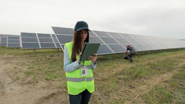 디지털 태블릿을 들고 태양 전지 패널 전력 농장에서 일하는 검사 엔지니어 여성. 태양광 패널 분야. 청정 에너지 생산. 친환경 에너지.