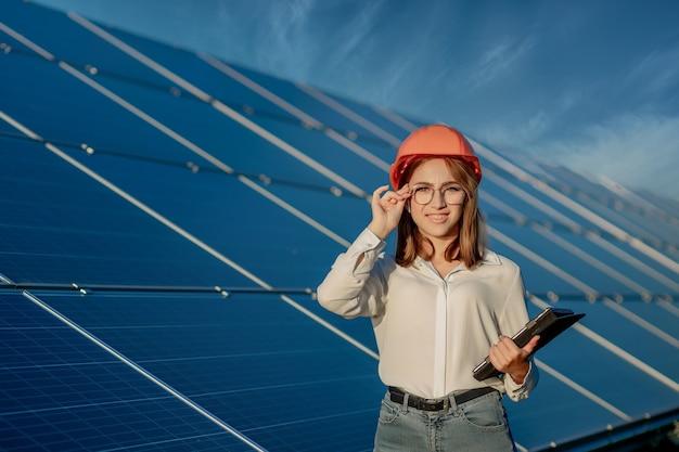 태양 전지 패널 전원 농장, 태양 광 전지 공원, 녹색 에너지 개념에서 일하는 디지털 태블릿을 들고 관리자 엔지니어 여자.