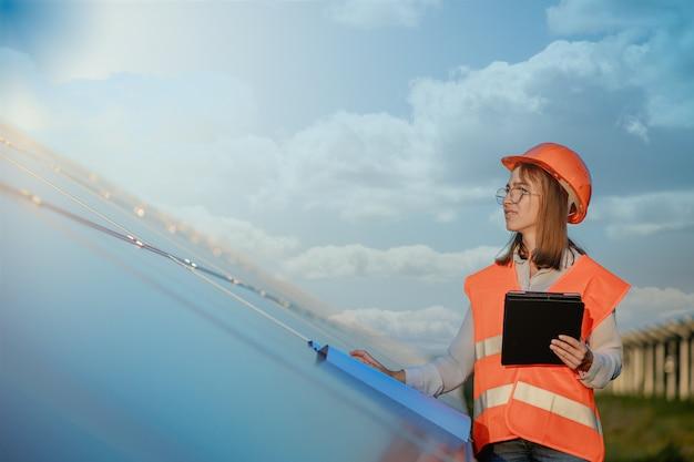 ソーラーパネルパワーファーム、太陽電池パーク、グリーンエネルギーコンセプトで働くデジタルタブレットを保持している検査エンジニアの女性。