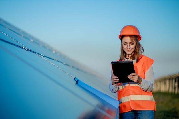 태양 전지 패널에서 작업하는 디지털 태블릿을 들고 관리자 엔지니어 여자
