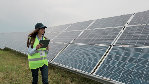검사 엔지니어 여성은 디지털 태블릿 pc로 재생 에너지 스테이션을 걷고 태양 전지판 설치를 확인합니다. 태양광 패널 분야. 청정 에너지 생산. 친환경 에너지.