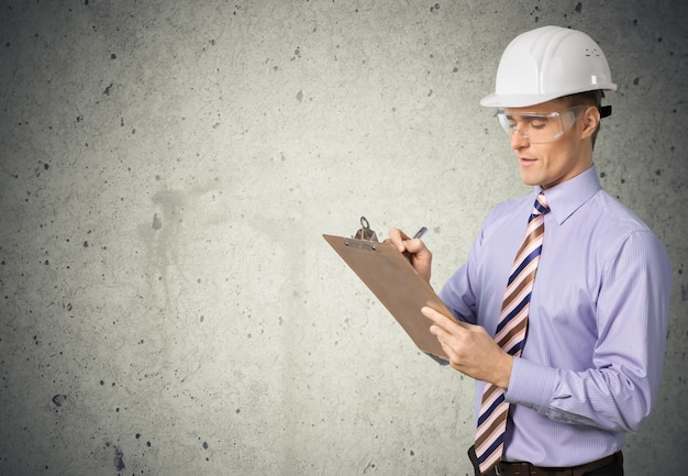 Inspector safety with glasses and hard hat holding clipboard on wall background