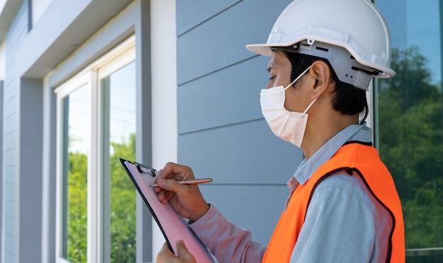 검사관이나 엔지니어는 바이러스 백신 마스크를 착용하고 건물 구조와 벽 페인트 요구 사항을 확인하고 있습니다.