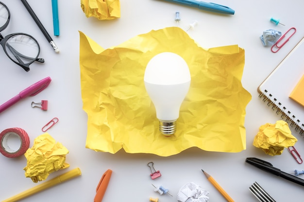 Inspiration creativity concepts with lightbulb in paper crumpled ball on worktable