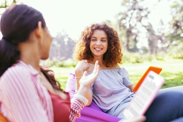 영감. 의자에 앉아 그녀의 동료와 이야기하는 기쁘게 곱슬 머리 여자