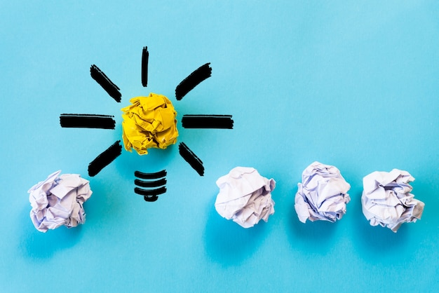 Inspiration idea concept. light bulb with crumpled colorful paper on blue background.