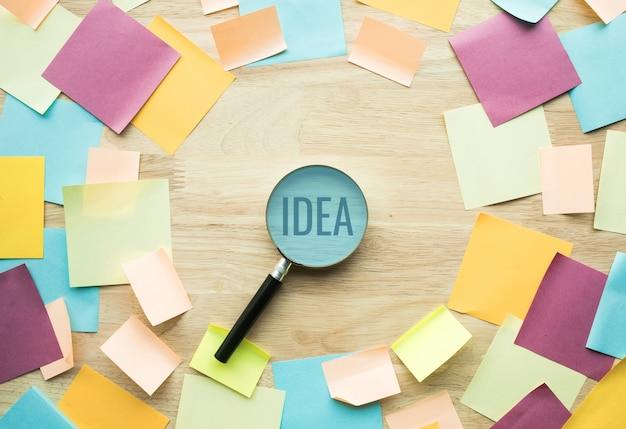 虫眼鏡とカラフルな便箋でインスピレーションのアイデアの概念