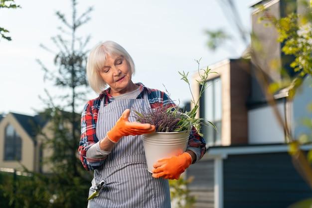 영감. 정원에서 시간을 보내는 동안 식물을 들고 영감을받은 좋은 여자