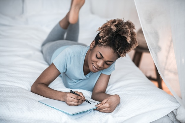 Inspiration. involved happy dark skinned woman lying on bed in light bedroom writing on notebook