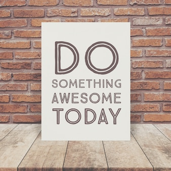 Inspiration Quote on paper at wooden table top and brick wall background