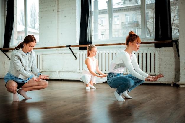 Вдохновение. рыжая учительница танцев в синих джинсах и ее ученики выглядят вдохновленными