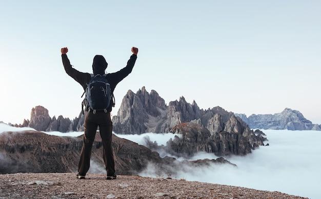 Вдохновение к успеху. путешественник поднял руки вверх на прекрасных дневных горах, полных тумана.