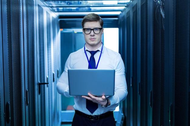 Вдохновение. хорошо сложенный вдохновленный сотрудник держит компьютер и работает на нем