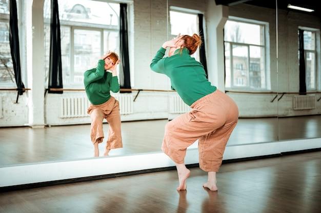 Вдохновение. молодая рыжеволосая учительница танцев с пучком волос выглядит вдохновенно, пока