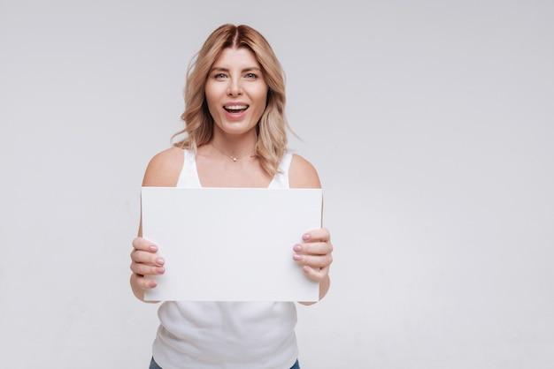Вдохновляющая радостная дама держит чистый лист бумаги и носит простую обычную одежду