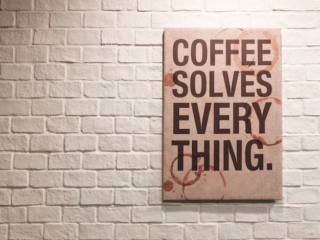Inspirational motivating quote about coffee on canvas frame hanging on brick wall in the cafe