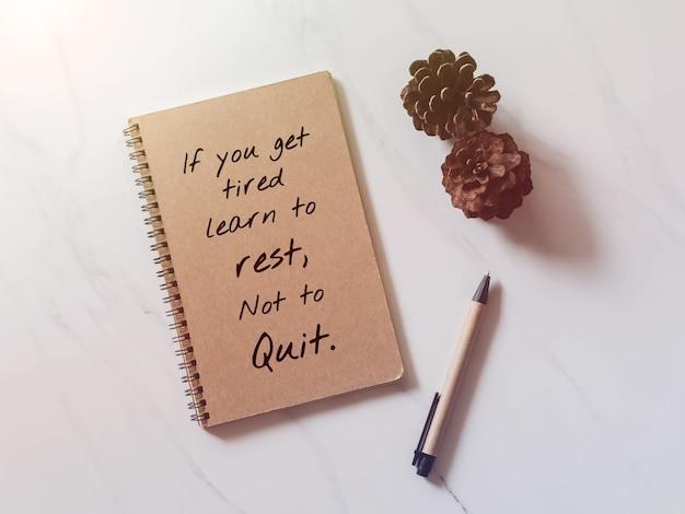 Вдохновенная мотивационная цитата на ноутбуке с сосновым конусом и ручкой