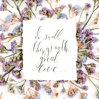 흰색 바탕에 파란색과 보라색 말린 꽃과 함께 종이에 붓글씨 스타일로 쓰여진 영감을주는 인용구