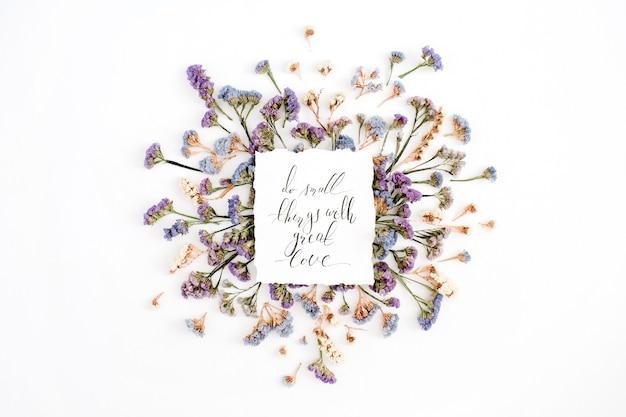 白地に青と紫のドライフラワーを紙に書道で書いた、「大きな愛を込めて小さなことをする」という心に強く訴える引用。フラットレイ、トップビュー