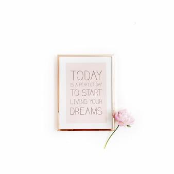 心に強く訴える引用「今日はあなたの夢を生き始めるのに最適な日です」。最小限の金色のフォトフレームと白地にピンクの牡丹の花