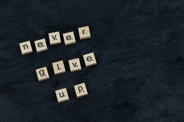 Inspirational quotes on a black board written with wooden dices
