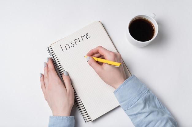 Женская рука пишет слова inspire в тетрадь. блокнот, ручка и кофе на белом