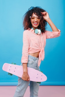 Inspired african female model in yellow sunglasses having fun. smiling mulatto girl with skateboard posing in room with blue interior.